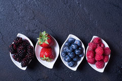 Berries : raspberries , blueberries , blackberries , strawberrie. S. Fresh summer berries in a white bowl on a stone background Royalty Free Stock Photography
