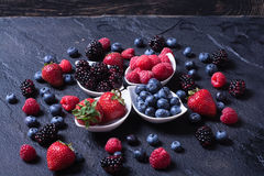 Berries : raspberries , blueberries , blackberries , strawberrie. S . Fresh summer berries in a white bowl on a stone background Stock Image