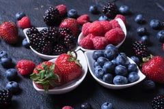 Berries : raspberries , blueberries , blackberries , strawberrie. S. Fresh summer berries in a white bowl on a stone background Royalty Free Stock Image