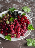 Berries - raspberries, gooseberries, red currants, cherries, black currants on a white plate Royalty Free Stock Images