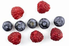 Berries of raspberry and blueberry are isolated on a white background. Berries of raspberry and blueberry by close up isolated on a white background Royalty Free Stock Images