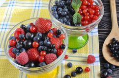 Berries of red-blue color close-up in a glass vase stock image