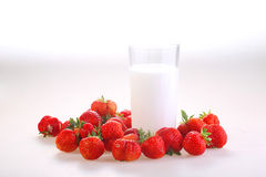 Berries of a red ripe strawberry and a transparent glass of milk. On a white background royalty free stock photo