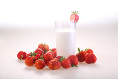 Berries of a red ripe strawberry and a transparent glass of milk. On a white background stock images