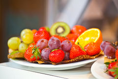 Berries of red strawberry and grapes lie on a pancake in buffet Royalty Free Stock Photography
