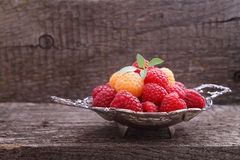 Berries red and yellow raspberries. In a metal bowl on a dark wooden background royalty free stock photography