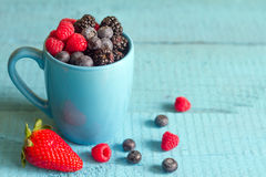 Berries spring fruits on blue wooden boards abstract still life. Closeup Royalty Free Stock Photo