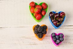 Berries, strawberries, blackberries cherry and blueberries in a heart-shaped plate on a white wooden old table close-up, autumn ha Royalty Free Stock Photography