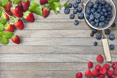 Berries Strawberries Blueberries Raspberries Background. Various fresh berries, strawberries, raspberries and blueberries around the edge of a wood background royalty free stock images