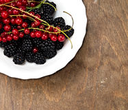 Berries in summer. A bowl of fresh summer berries on a rustic wooden background stock photo