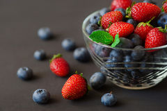 Berries, summer fruit on black wooden table. Healthy lifestyle concept, blackberries in bowl, top view, close-up. Top view of Strawberry and blueberry in glass Stock Photography