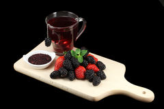 Berries and tea. Forest berries and tea on a wooden board isolated on a black background stock photography