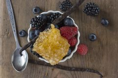Berries, Vanilla Bean and Honeycomb on wooden surface. Blackberries, Raspberries, Blueberries in a white bowl, Vanilla Bean and Honeycomb with a spoon on a Royalty Free Stock Images