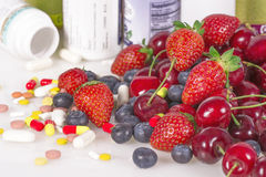 Berries, vitamins and nutritional supplements Stock Photography