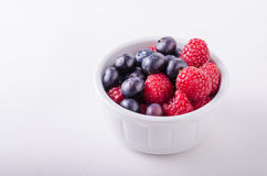 Berries in white bowl. Forest fruit white background Royalty Free Stock Photography