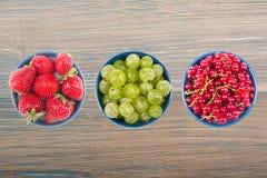 Berries on Wooden background, bowl of Cherry, currant, blueberries, gooseberries, raspberries, blackberries. Various summer Fresh berries in a bowl. Antioxidants Stock Photography