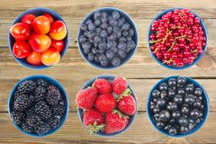 Berries on Wooden background, bowl of Cherry, currant, blueberries, gooseberries, raspberries, blackberries. Various summer Fresh berries in a bowl. Antioxidants Stock Images