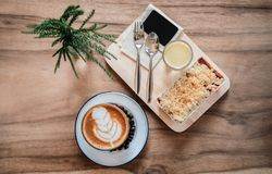 Berry and apple crumble on wood tray with hot latte coffee stock photos