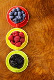 Berry assortment - raspberries, blackberries, strawberries, blueberry. On a wooden background Stock Images
