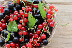 Berry background. Black berries and red currants are in a brown wicker basket on old wooden surface. Stock Photo