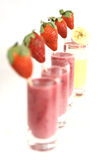 Berry and banana smoothies. A row of strawberries and berry smoothies with an banana smoothie Stock Images