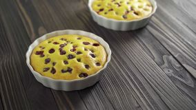 Berry biscuit mini tarts in a baking dish. Tasty dessert with currants. Dark wooden background stock video
