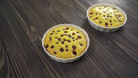 Berry biscuit mini tarts in a baking dish. Tasty dessert with currants. Dark wooden background stock footage