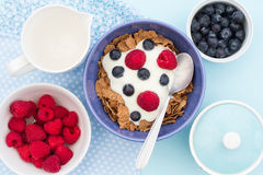Berry, Bran And Yoghurt Breakfast. A healthy breakfast of Bran Flakes, raspberries, blueberries and natural yoghurt with a blue colour theme. Top down image from stock photo