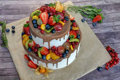 Berry cake. The beautiful berry fruit cake from two tiers covered with chocolate on a wooden table royalty free stock photo
