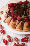 Berry cake with chocolate icing close-up on a plate. vertical Royalty Free Stock Images