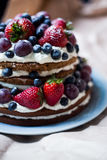 Berry cake. Chocolate sweet berry naked cake with cream strawberry blueberry mint grape stock photo