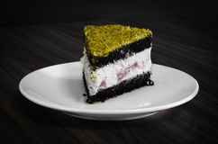 Berry and chocolate cake topped with pistachio served in white plate on wooden table Stock Photography