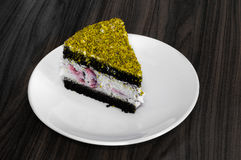 Berry and chocolate cake topped with pistachio served in white plate on wooden table Royalty Free Stock Photography