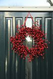 Berry christmas wreath. With decorations on a door stock photography