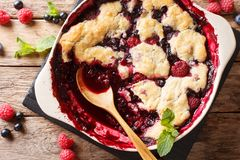 Berry cobbler with currants, raspberries and blueberries decorat. Ed with mint close up on the table. Vertical top view from above Royalty Free Stock Images