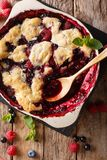 Berry cobbler with currants, raspberries and blueberries decorat. Ed with mint close up on the table. vertical top view from above Stock Images