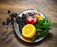 Berry cocktail in glass with ice, lemon and mint leaves on a wooden table . Stock Photography