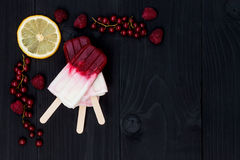 Berry coconut ice pops - popsicles - over old rustic wooden background. Top view. Stock Photo