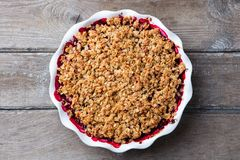 Berry crumble, crisp in baking dish. Wooden background. Top view. Berry crumble, crisp in baking dish. Wooden background. Top view stock images