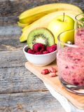 Berry dessert smoothie banana Kiwi Apple Parsley Raspberry Nuts for Breakfast.  Stock Photo