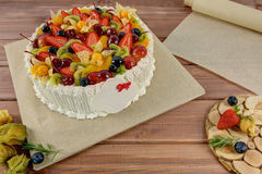 Berry festive cake. On a paper substrate on a wooden table Royalty Free Stock Images