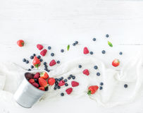 Berry frame with copy space on right. Metal bucket, strawberries, raspberries, blueberries and mint leaves, white wooden. Background, top view, copy space Royalty Free Stock Images
