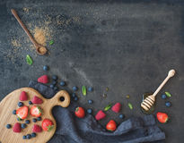 Berry frame with copy space on right. Strawberries, raspberries, blueberries and mint leaves. Honey, cane sugar, dark grunge background, top view, copy space Stock Photo