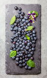 Berry fresh blueberries with mint leaves on black slate board. Berry fresh blueberries with fresh mint leaves and edible flowers on black slate board. Stone gray Stock Image