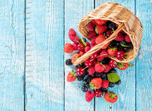 Berry fruit in basket placed on old wooden planks Stock Photos