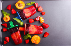 Berry and fruit ice cream pops on black surface Stock Photo