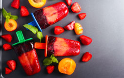 Berry and fruit ice cream pops on black surface Stock Photography