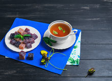 Berry-fruit marmalades cubes. Tea and mint leaves on a dark black wooden background, empty place for text Stock Photos