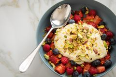 Berry fruit salad with strawberries, blueberries, raspberry, pistachio, lemon zest and linseed oil quark cream in blue bowl for stock photo
