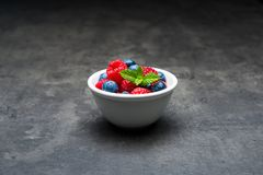 Berry fruit with waterdrops in white ceramic bowl on dark concre. White ceramic bowl with berry fruit, waterdrops on blueberries and raspberries with mint leaves Royalty Free Stock Images